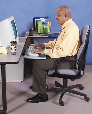 Man seated at computer with monitor at eye level and her feet flat on support.