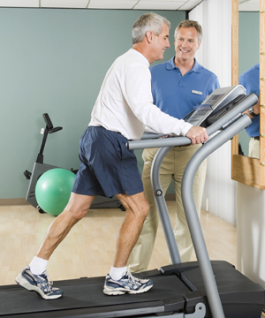 Man on treadmill with health care provider standing next to treadmill, supervising man's exercise.