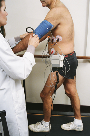Man with wires attached to chest walking on treadmill. Health care provider is taking man's blood pressure.