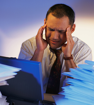 Man holding his head in pain, surrounded by paper work and a lab top.