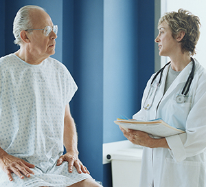 Senior male patient in hospital gown talking with female doctor.