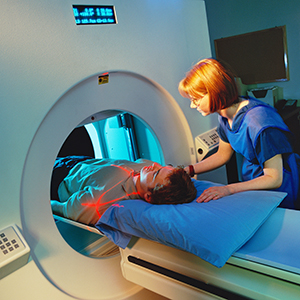 Man in a CAT scan machine. Health professional at side.