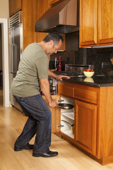 Image of man bending to retrieve a pan from a lower cabinet in kitchen