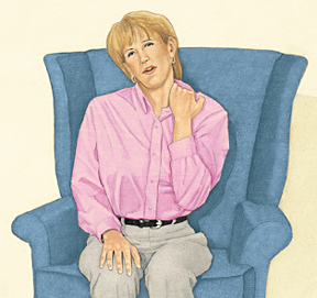 Woman in chair rubbing neck