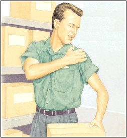 Man working in warehouse holding shoulder in pain.